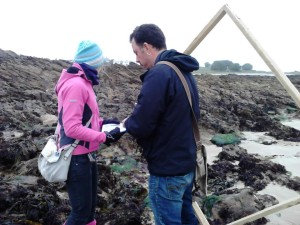 Juan the Trust's Marine Officer doing a survey to measure the diversity of life on the beach with Melanie
